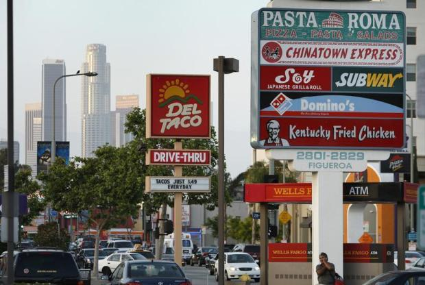 Signs of fast food restaurants are seen along a busy street in Los Angeles